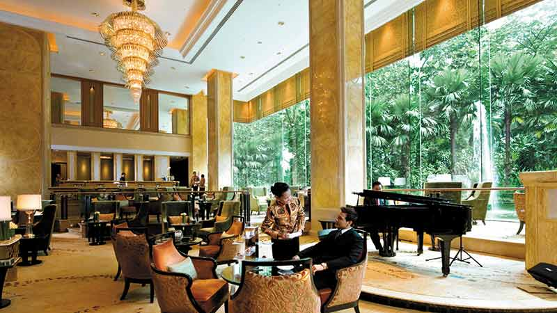 A guest being served by a staff member in the lounge of Shangri-La-Hotel, Kuala Lumpur