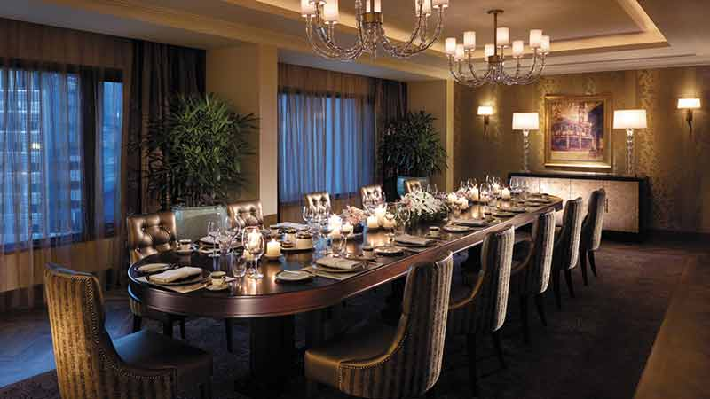 12 seater dining table in the Malaysian Suite lit by chandaliers at the Shangri-La Hotel in Kuala Lumpur