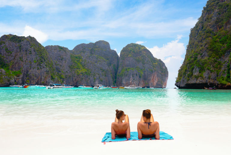 Two girls resting on the white sand in Maya Bay