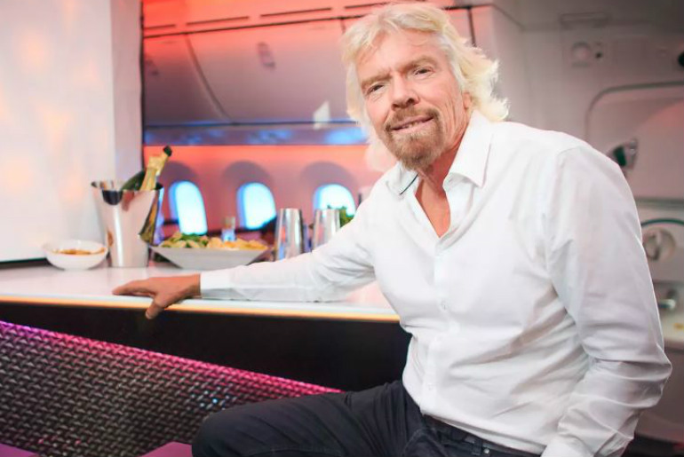 Sir Richard Branson sitting in the onboard bar of a Virgin Atlantic Plane