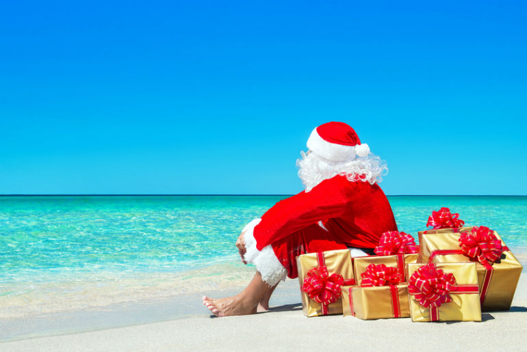 Santa Claus on a tropical beach with Christmas presents