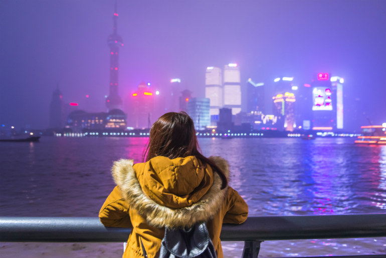Lady looking at the city lights at night in Shanghai