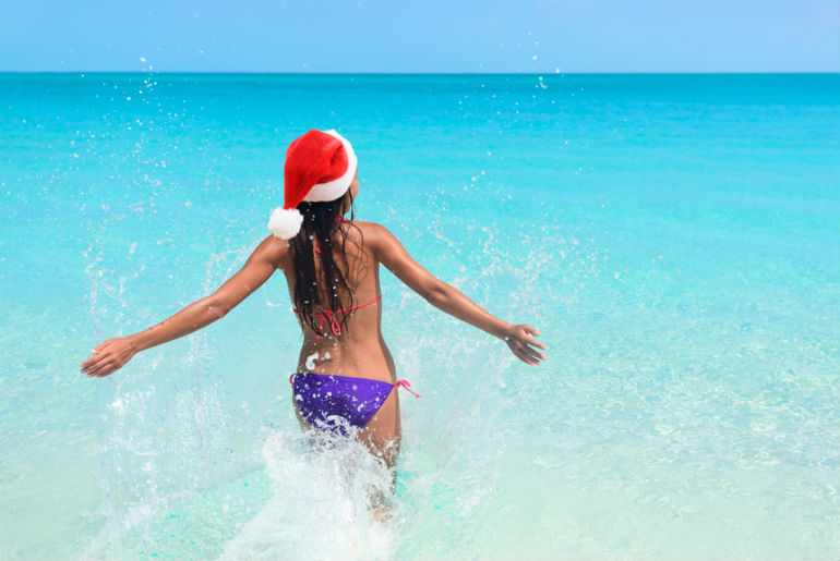 a girl wearing a Santa Claus hat while going into the Thailand ocean
