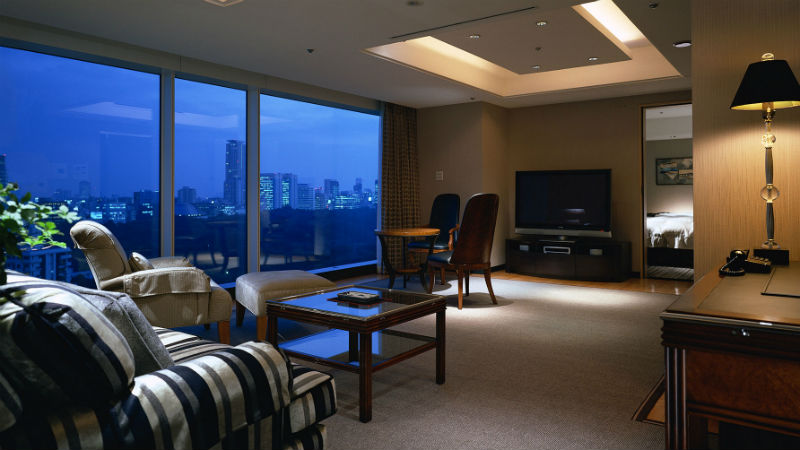 The Main Presidential Suite HIROSHIGE at the New Otani Tokyo Hotel, showing living room and a wide window over looking Tokyo city at night