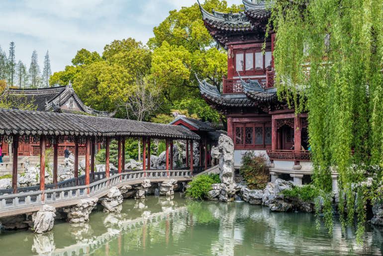 Yuyuan Garden showing the temple and the old bridge going over the lake gardens