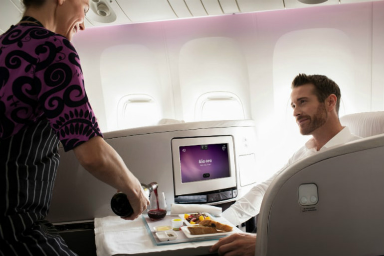 a man being served dinner by a Air New Zealand stewardess