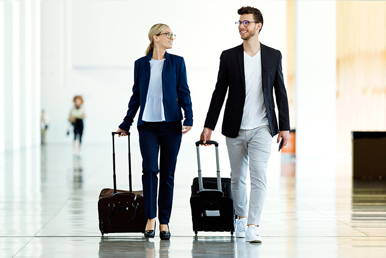smartly dressed couple walking through the airport