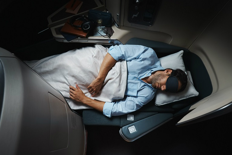 a man sleeping on the lie flat bed in cathay pacific business class cabin