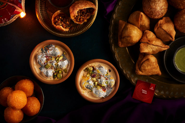 A mixture of Diwali foods being served in bowls at lounges
