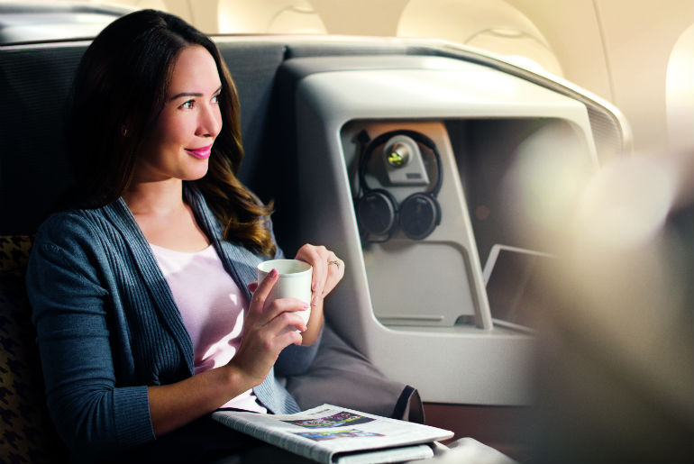 Woman relaxing in a Singapore Airlines business class seat