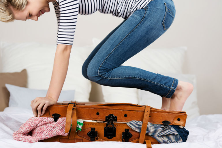 A lady jumping on her luggage to close