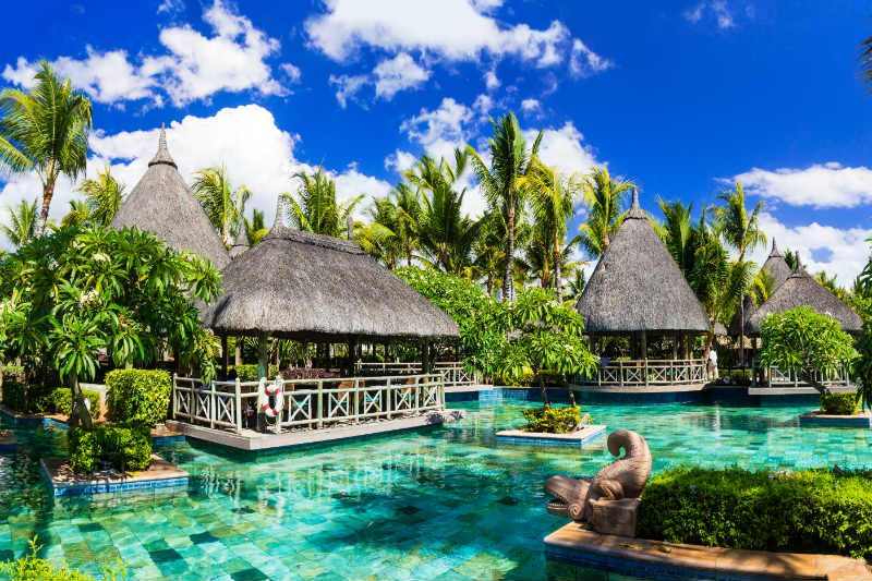 Resort swimming pool surrounded by palm trees in Mauritius