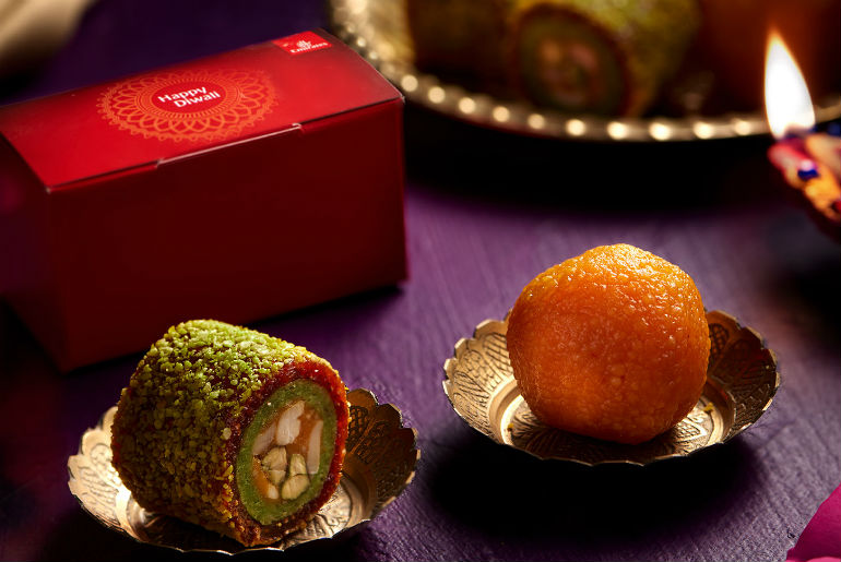 a mixture of Diwali foods with a Emirates box