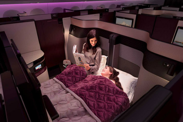 A mother and daughter in Qatar Business Class lie flat beds