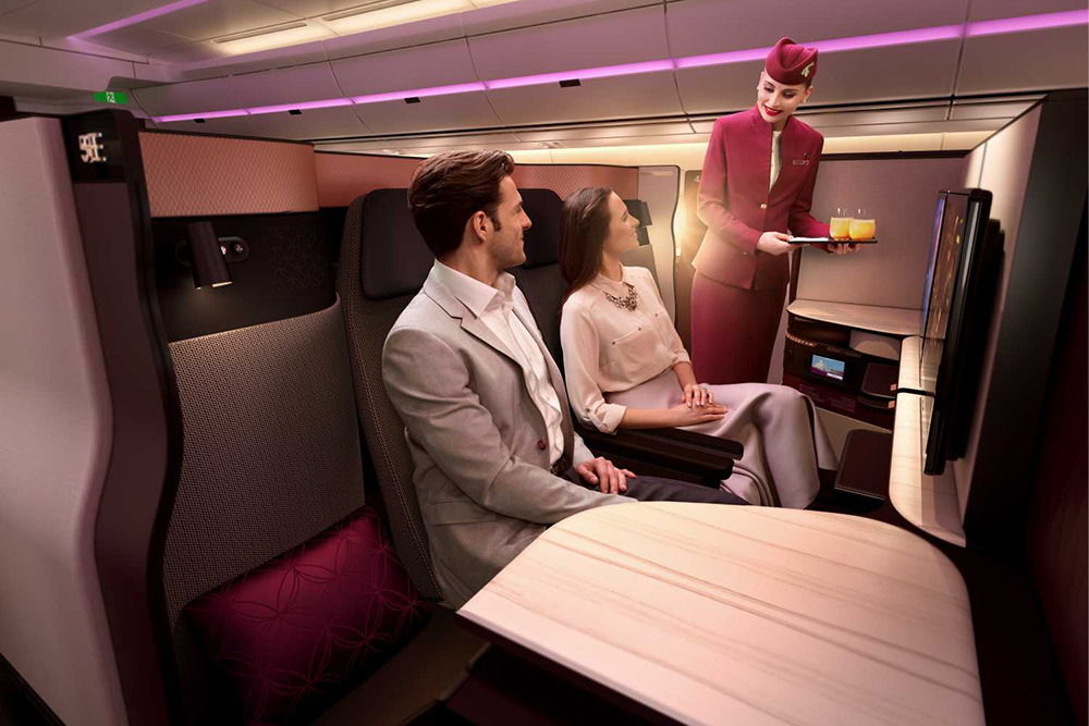 Couple sitting in the Qatar Airways Qsuite being served by a stewardess