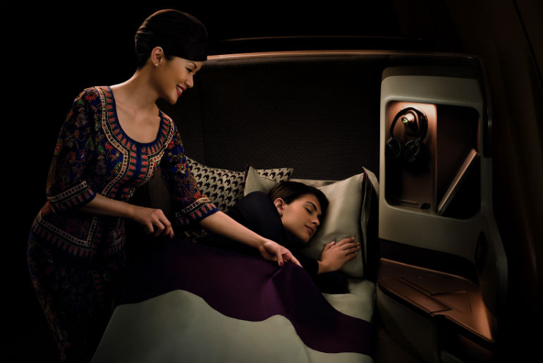 A Singapore Airlines staff putting a blanket on a sleeping customers