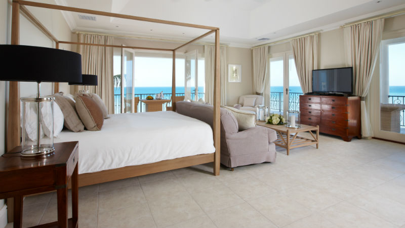 Four post bed in a Bedroom with sea views at Blue Waters Antigua