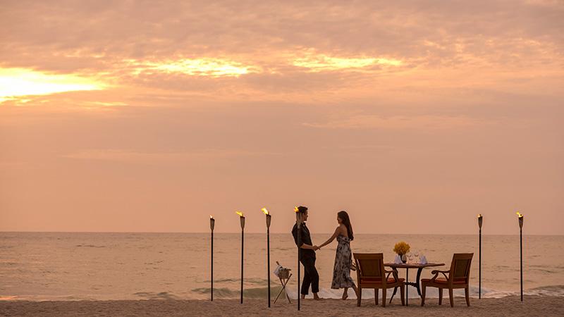Couple dining on the beach at sunset at Angsana Laguna Phuket