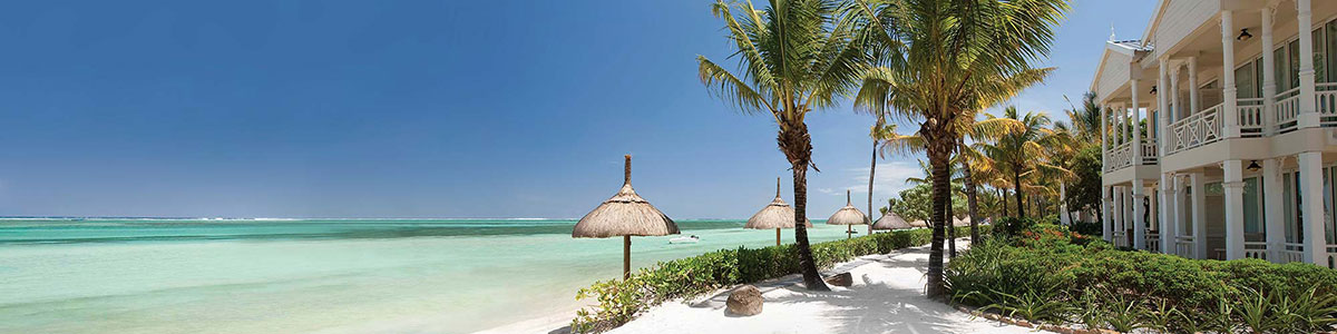 White sand beach with umbrellas at Heritage Le Telfair in Mauritius