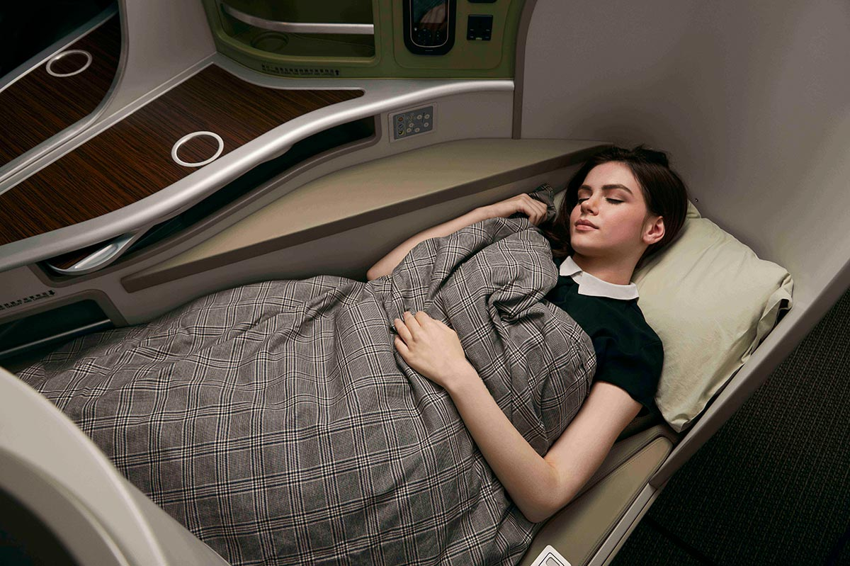 Woman sleeping in the EVA Air business class fully flat bed