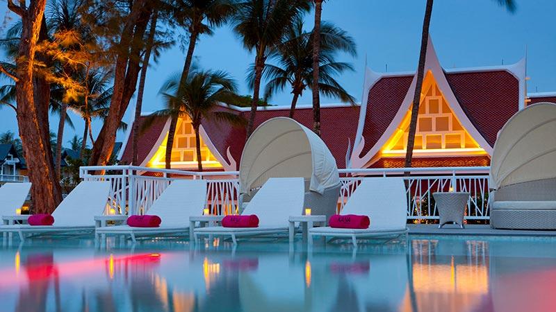 Pool loungers at sunset at the XANA Beach Club at Angsana Laguna Phuket