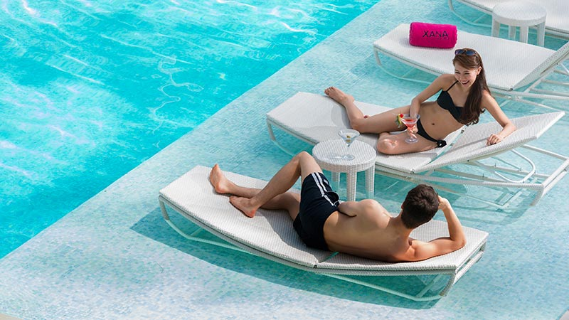 Couple relaxing by the XANA pool on sun loungers at Angsana Laguna Phuket