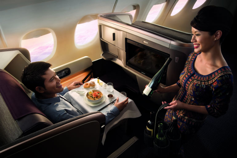 A man in business class Singapore Airline seat being served book the cook option