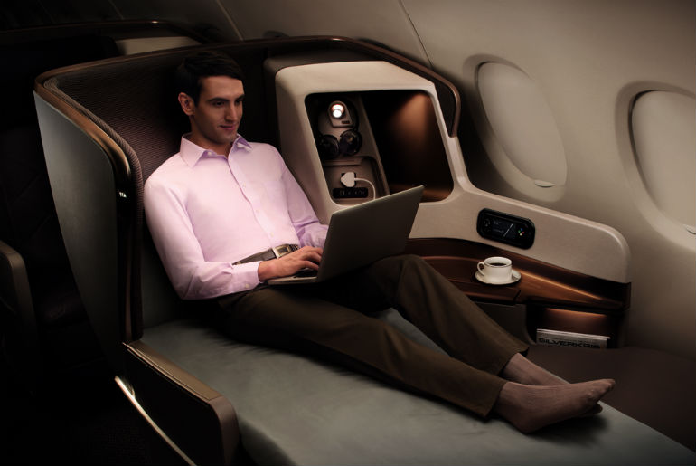 a business man on his laptop in a Singapore Airlines business class seat