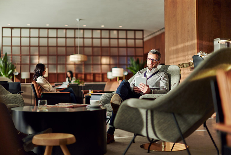Man sitting in Cathay Pacific business class lounge