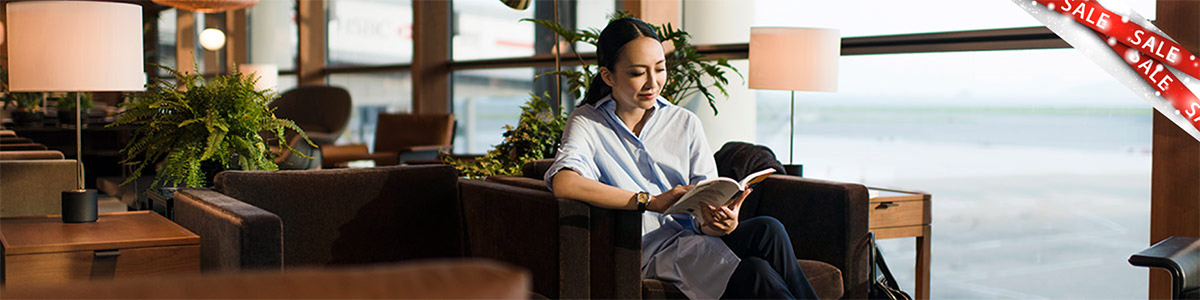 Woman in a Cathay Pacific Business Class Lounge with sale banner