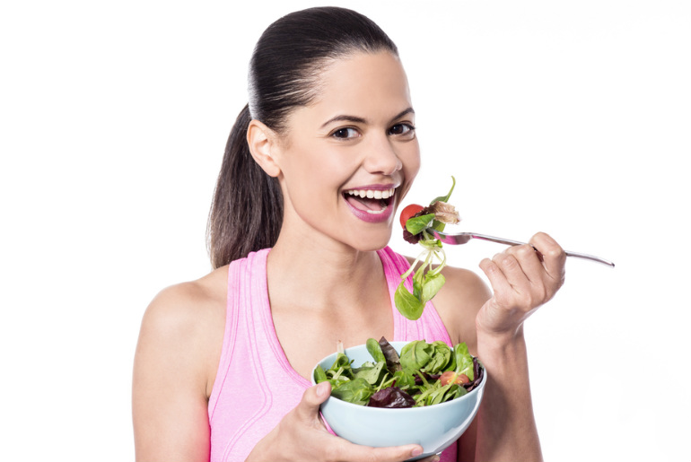 A lady eating a bowl of salad