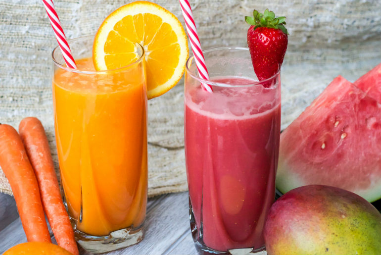 Fresh juices surrounded by vegetables and fruit