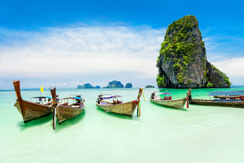 Longtail boats in clear blue water with limestone cliffs behind in Phuket Thailand