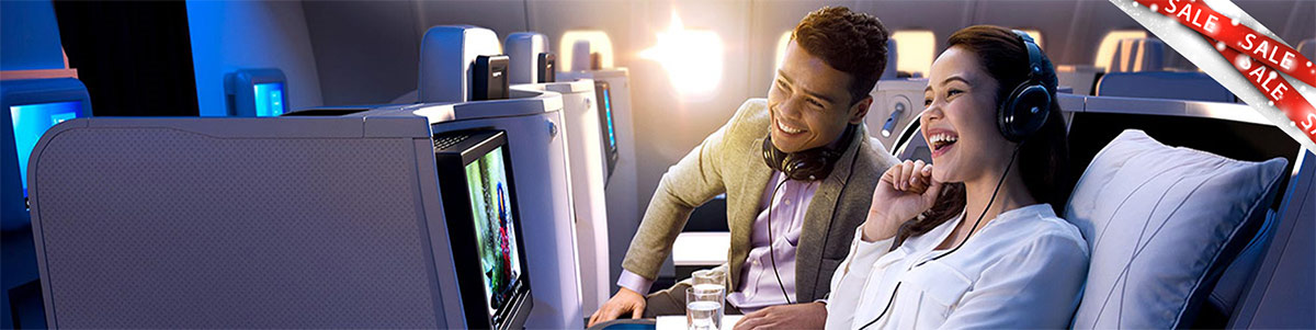 Couple in Malaysia Airlines business class cabin with sale banner