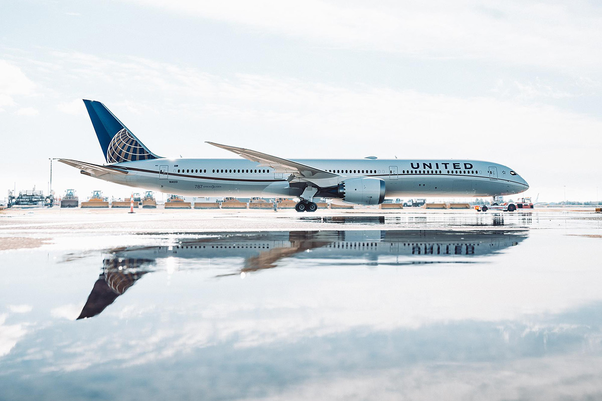 United Airlines Dreamliner on a runway with a reflection in water