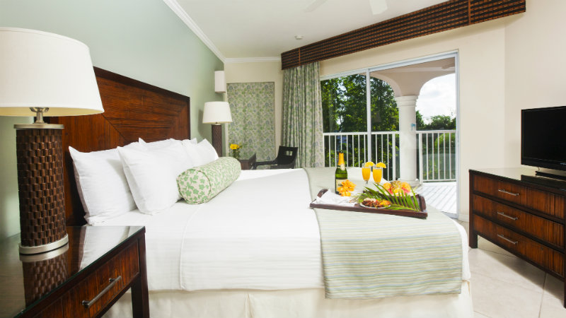 Bedroom and balcony of the One Bedroom Garden view Spa Suite at St James's Club Morgan Bay