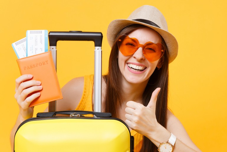 Girl traveller a suite case with thumb up