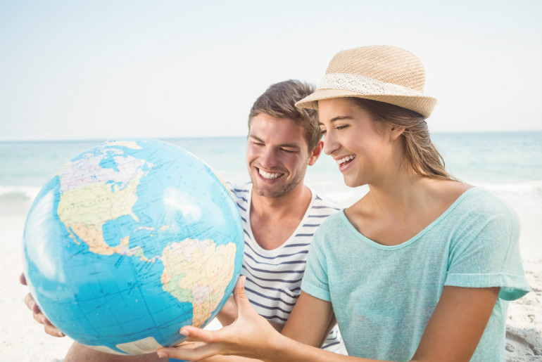 Couple looking at globe to pick their stopover destination