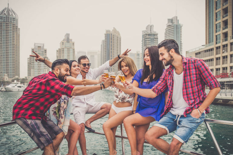 Group of people cheers drinks on a boat while on a Dubai stopover