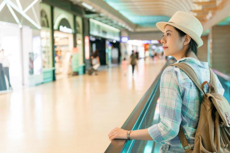 A lady looking at shops going through Hong Kong Airport