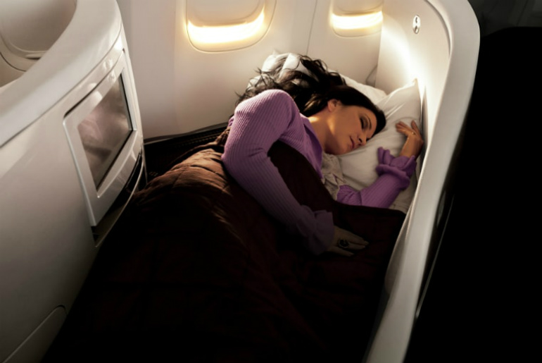 a lady sleeping in Air New Zealand business class cabin