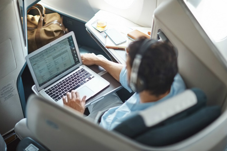 Cathay Pacific business class passenger working on his laptop