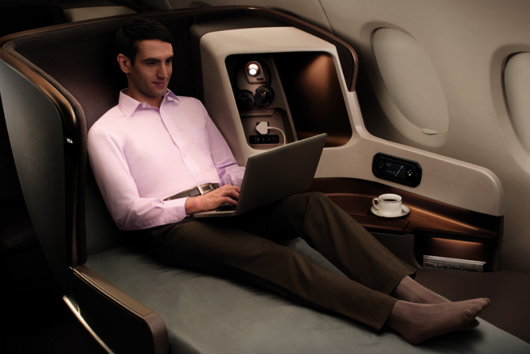 A man with a laptop in Singapore Airlines business class seat