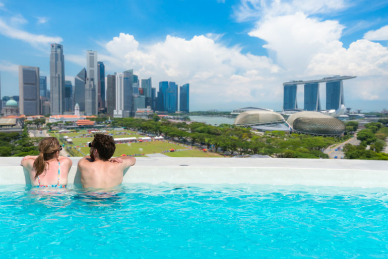 Couple sitting in a roof top Singapore swimming pool