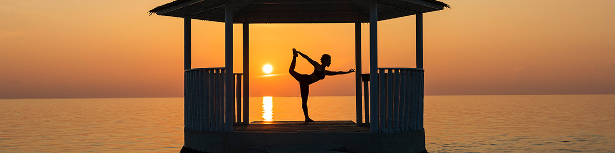 Woman doing yoga at sunset at the Centara Ras Fushi Resort in the Maldives