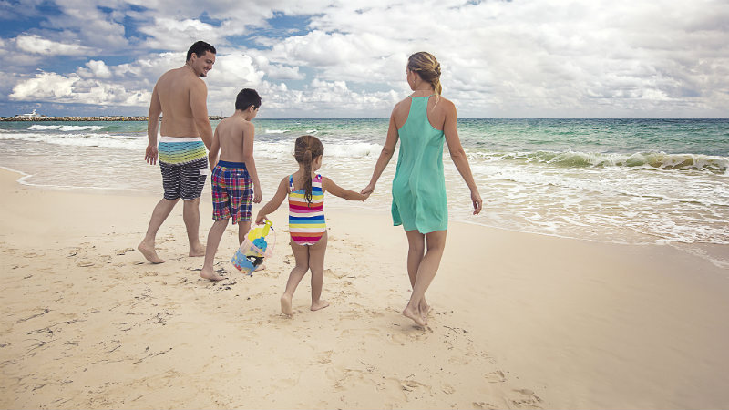 A family on the beach at the Grand Residences Riviera Cancun