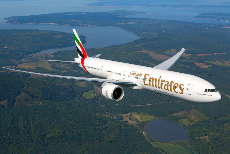 Emirates B777 flying across green fields