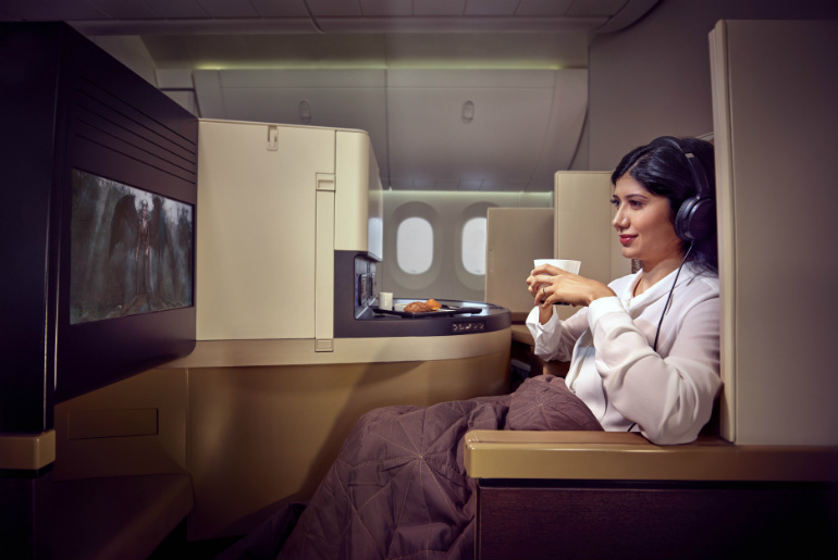 A lady watching a film in Etihad Airways business class 787