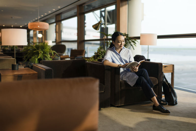 a lady sitting in The Pier Lounge, Cathay Pacific