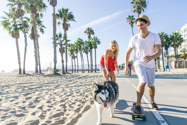 Couple skating with dog in Santa Monica